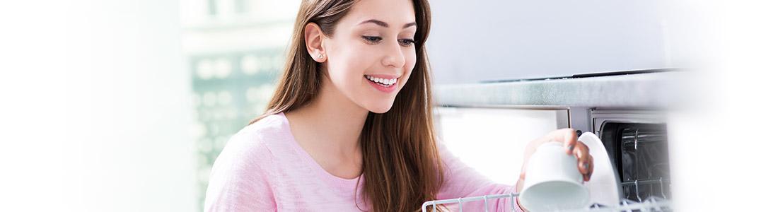 Eine junge Frau räumt die Spülmaschine ein