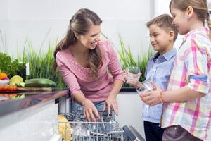 Mutter zeigt Kindern die Spülmaschinen-Funktionen