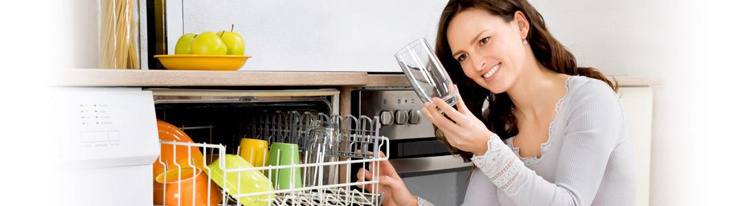 Frau freut sich über sauberes Geschirr aus neuer Spülmaschine