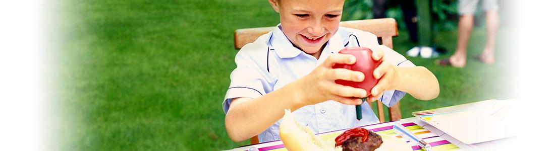 Junge drückt genüsslich Ketchup auf seinen Grillteller