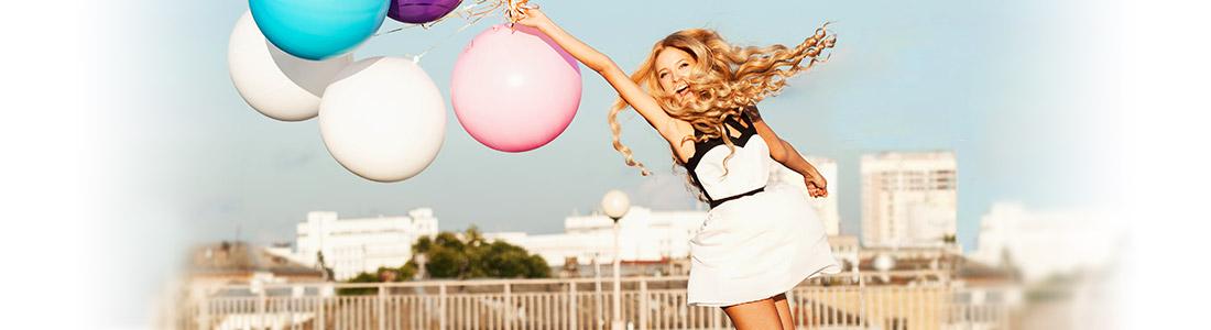 Frau im Sommerkleid hält bunte Ballons im Wind