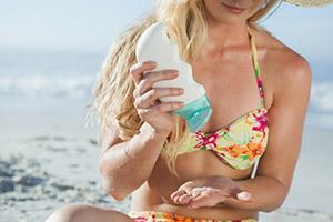Frau im Bikini cremt sich mit Sonnencreme ein