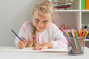 Mädchen malt an aufgeräumtem Schreibtisch
