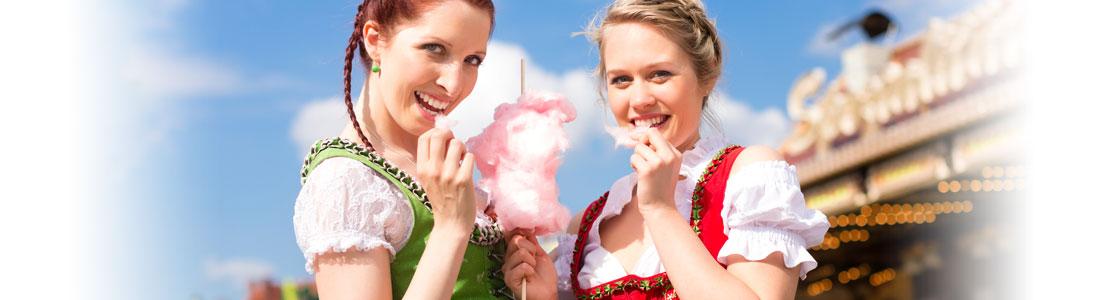 Zwei Freundinnen essen Zuckerwatte auf dem Oktoberfest