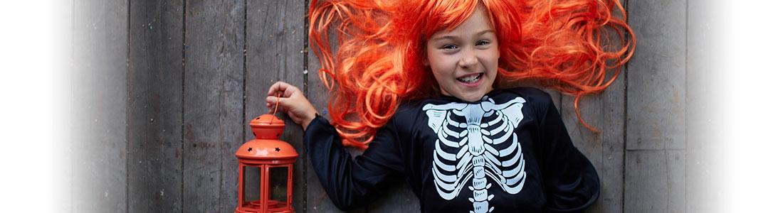 Mädchen im Skelettkostüm mit orangener Perücke freut sich über Halloween