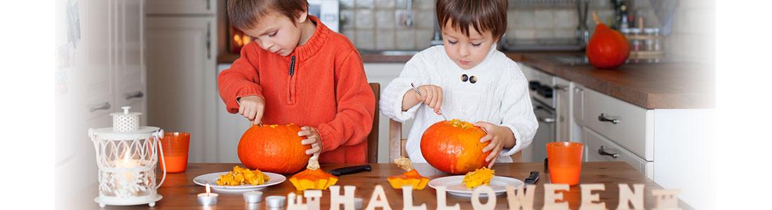 Zwei Jungen schnitzen Kürbisse an Halloween