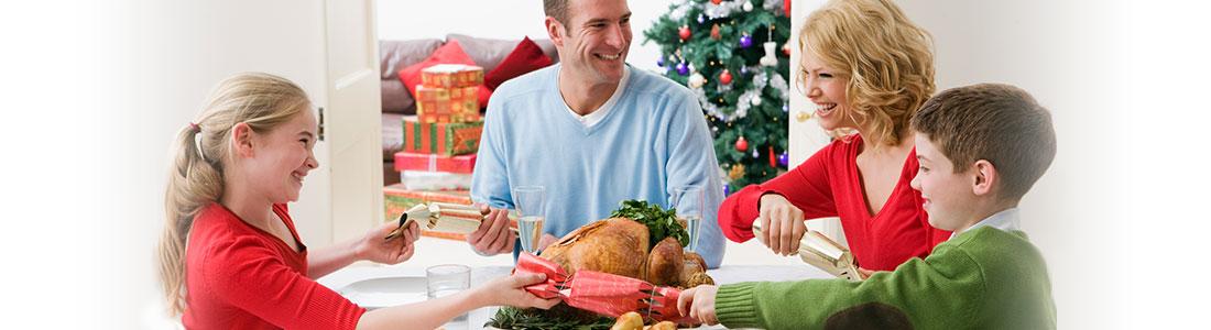 Familie am weihnachtlichen Tisch mit selbstgebastelten Christmas Crackern