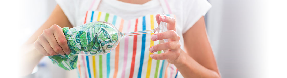Frau trocknet Weinglas nach dem Spülen