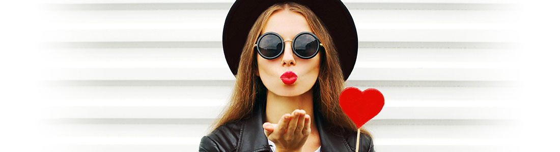 Frau mit gebasteltem Herz in der Hand wirft Kussmund