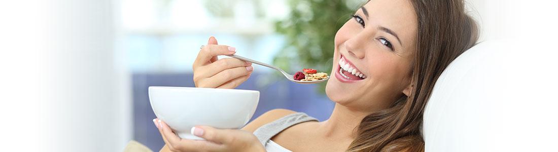 Frau mit Müslischale freut sich über Rezepte gegen Frühjahrsmüdigkeit