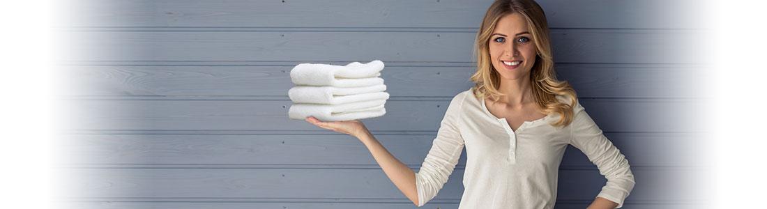Frau hält Wäschestapel mit glatter Wäsche ohne Bügeln