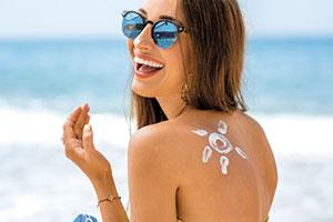 Frau am Strand mit Sonne aus Sonnencreme auf dem Rücken