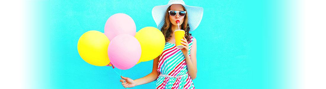 Junge Frau hält bunte Luftballons in der Hand und trinkt einen Smoothie