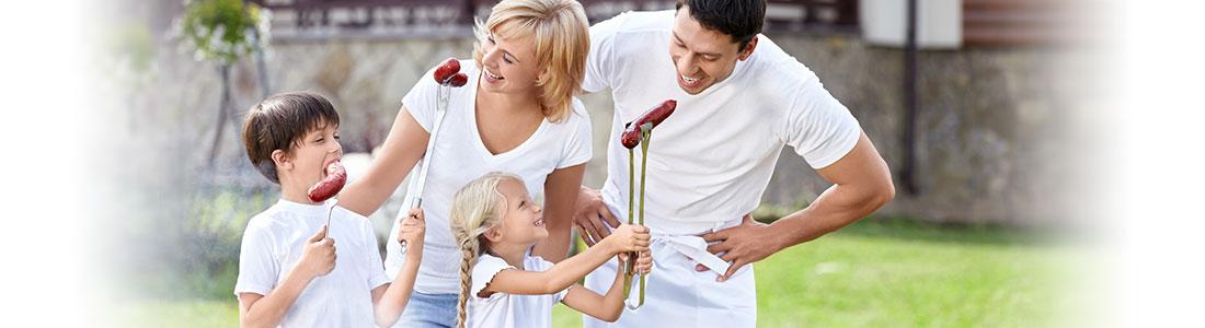 Familie mit Grillbesteck und Grillwürstchen