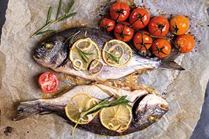 Gegrillter Fisch auf Pergamentpapier mit Kräutern und Gemüse