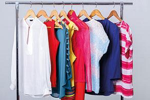 Des vêtements colorés sont suspendus à des cintres sur une tringle à vêtements