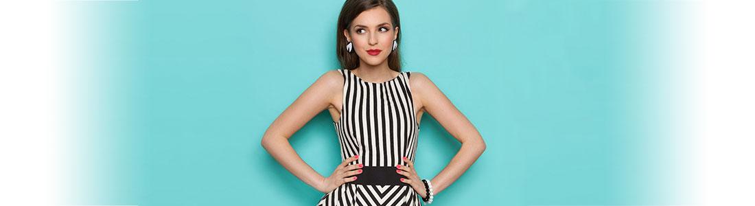 Junge, modische Frau in schwarz-weiß gestreiftem Kleid stemmt die Hände in ihre Hüften