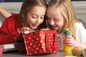 Zwei Mädchen sitzen am Tisch und inspizieren den Inhalt einer rot-weiß gepunkteten Kühltasche