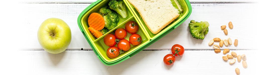 Eine gefüllte Brotdose mit Sandwich und frischem Obst und Gemüse