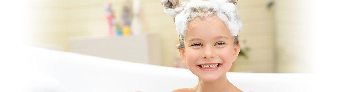 Ein Mädchen in der Badewanne mit viel Schaum auf dem Kopf