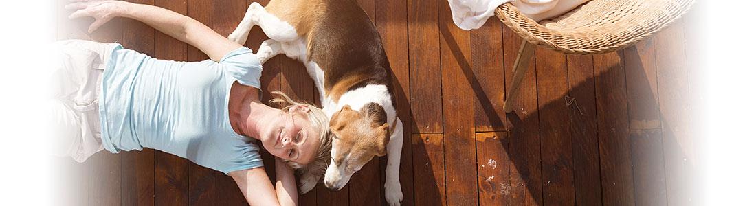 Eine Frau und ein Hund liegen entspannt auf der Terrasse