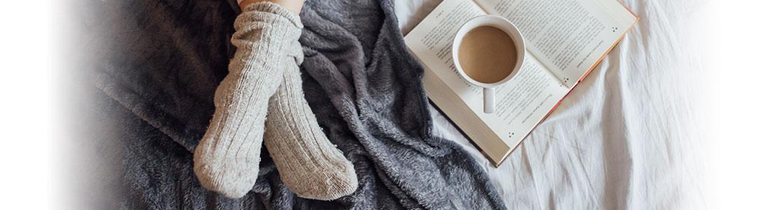 Zwei Füße in dicken Wollsocken, ein offenes Buch und eine Tasse Kaffee