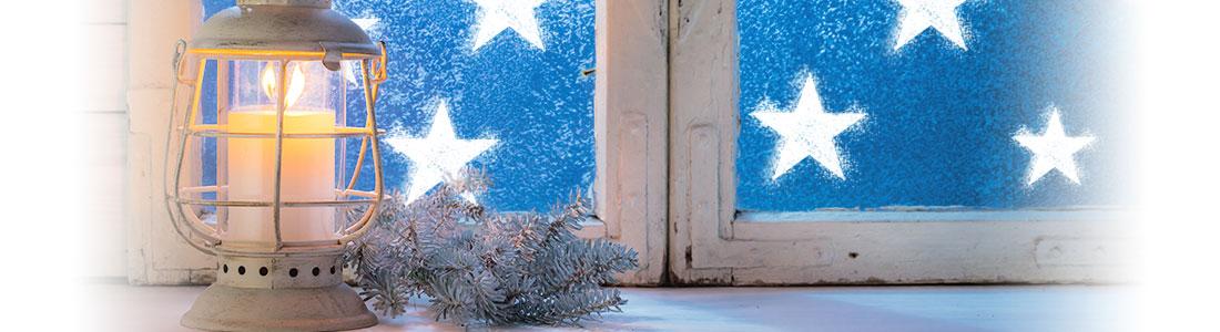 Weihnachtliche Fensterdeko aus Schneespray und ein Windlicht auf der Fensterbank