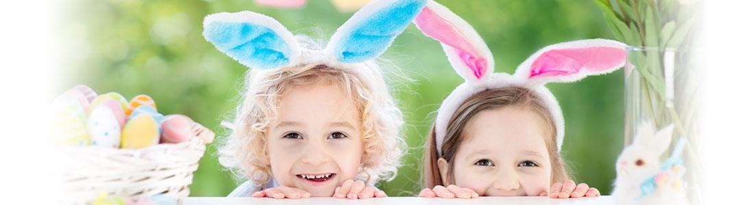 Zwei Kinder mit Hasenohren und Osterdeko