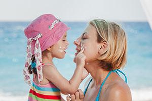 Mutter mit Tochter am Strand und Sonnencreme