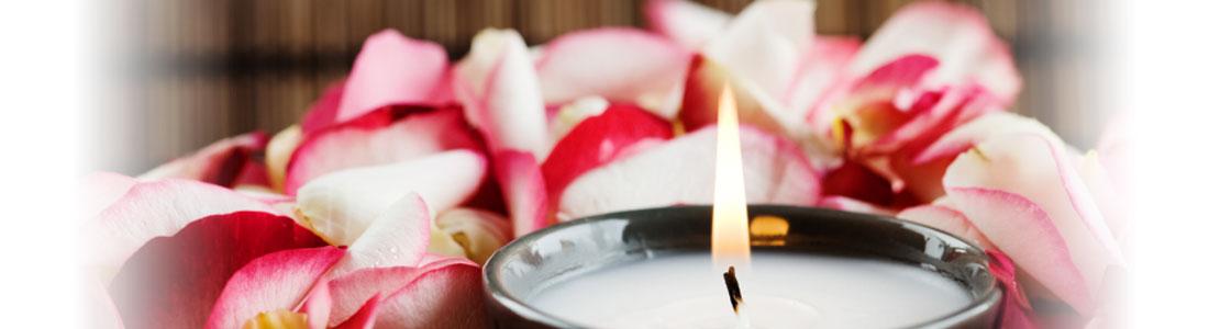 Eine brennende Kerze und Blütenblätter